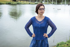 Portrait of young woman in blue clothes against a dutch canal Stock Photo