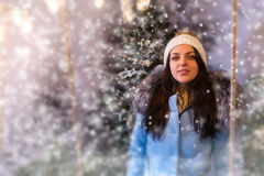 Portrait of young woman in blue down jacket standing in a snow-c Royalty Free Stock Photos