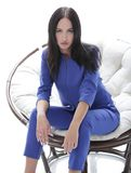 Portrait of a young woman in a blue suit sitting on a soft chair Stock Image