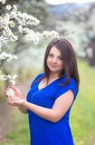Portrait of young woman in blue top with long dark hair near blossoming plum tree, waist up, looking straight to the camera royalty free stock photo