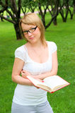 Portrait of young woman with book and glasses Royalty Free Stock Photo
