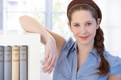 Portrait of young woman at bookshelf smiling Stock Photos