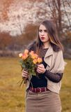 Portrait of a young woman with a bouquet of roses. In the autumn season Royalty Free Stock Photos