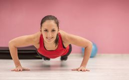 Young Woman Doing Pushups. Portrait of a young woman with braces doing pushups in a gym Stock Photos