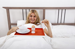 Portrait of young woman with breakfast tray in bed Stock Photography
