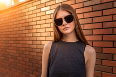 Portrait of Young Woman on Brick Wall Background. Stock Photo