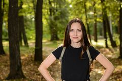 Portrait of a young woman brunette in a black t-shirt and a backpack, standing on the path a green Park in the background in the r. Ays of the bright sun Stock Photography