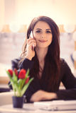 Portrait of young woman with bunch of tulips, laptop and mobile Royalty Free Stock Photo