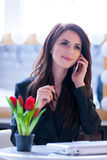 Portrait of young woman with bunch of tulips, laptop and mobile Stock Photo