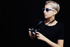 Portrait of young woman with camera. On black background Stock Image