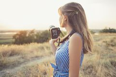Portrait of a young woman with a camera, nature photographer in the field royalty free stock image