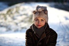 Portrait of a young woman with a cap. Beautiful young woman in a park in winter time Royalty Free Stock Image