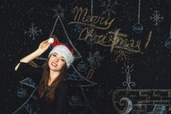 Portrait of a young woman in a cap of Santa Claus on Christmas background Stock Photography