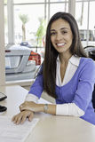 Portrait of young woman at car showroom Stock Image
