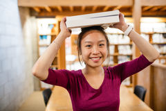 Portrait of young woman carrying book on head Stock Photography