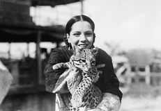 Portrait of a young woman carrying a cheetah cub and smiling stock photo