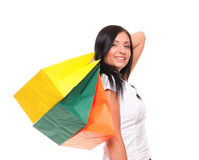 Portrait of young woman carrying shopping bags against white bac Stock Images