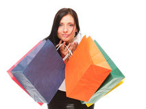 Portrait of young woman carrying shopping bags against white bac Stock Photos