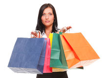 Portrait of young woman carrying shopping bags against white bac Royalty Free Stock Image