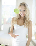 Portrait of young woman catching apple in kitchen Royalty Free Stock Photo