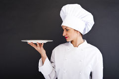 Portrait of young woman chef with plate Royalty Free Stock Photo