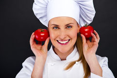 Portrait of young woman chef with tomatos over dark background Stock Photos