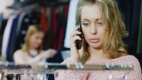 Portrait of a young woman chooses a dress in the store, talking on a cell phone. stock footage