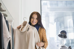 Portrait of young woman choosing sweater in store Stock Photography