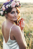 Portrait of young woman with circlet of flowers on head. Portrait of young beautiful woman circlet of flowers on head outdoors Royalty Free Stock Images
