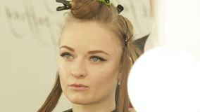 Portrait young woman with clamp on hair during haircutting in hairdressing salon. Female hair model while haircut stock video footage