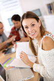 Portrait of young woman in classroom with schoolmates Stock Image