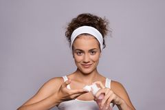 Portrait of a young woman cleaning face in a studio, beauty and skin care. A portrait of a young woman cleaning face in a studio, beauty and skin care royalty free stock image