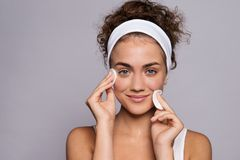 Portrait of a young woman cleaning face in a studio, beauty and skin care. A portrait of a young woman cleaning face in a studio, beauty and skin care royalty free stock photos