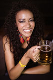 Portrait of young woman clenching teeth while holding beer mug Royalty Free Stock Photo