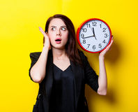 Portrait of the young woman with clock. Portrait of the beautiful young woman with red clock on the yellow background Royalty Free Stock Photography