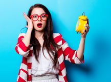 Portrait of the young woman with clock. Portrait of the beautiful young woman with yellow clock on the blue background Royalty Free Stock Photo