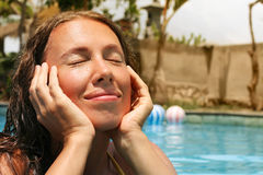 Portrait of young woman with close eyes and hands. Portrait of young smiling woman with close eyes and hands on her face in the swimming pool Stock Photos