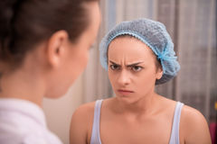 Portrait of a young woman. Close-up portrait of angry young women looking at her doctor with irritation after a professional cosmetology procedures in beauty spa Royalty Free Stock Photography