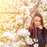 Portrait of a young woman with closed eyes in apple trees on a sunny day. Dark hair