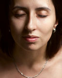 Portrait of young woman with closed eyes. On the dark background Royalty Free Stock Image