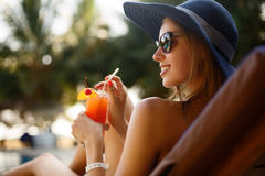 Portrait of young woman with cocktail glass chilling in the tropical sun near swimming pool on a deck chair with palm stock photo