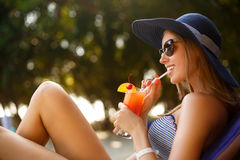 Portrait of young woman with cocktail glass chilling in the tropical sun near swimming pool on a deck chair with palm Royalty Free Stock Images
