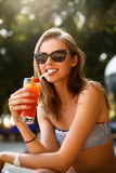 Portrait of young woman with cocktail glass chilling in the tropical sun near swimming pool on a deck chair with palm. Portrait of young woman with cocktail Stock Photography