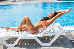 Portrait of young woman with cocktail glass chilling in the tropical sun near swimming pool on a deck chair . Vacation concept. Portrait of young woman with Stock Photos