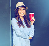 Portrait of young woman with coffee cup against black wall. Royalty Free Stock Image