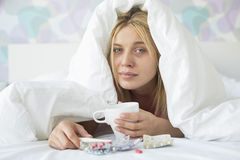 Portrait of young woman with coffee mug and medicines suffering from fever while covered in quilt on bed Stock Images