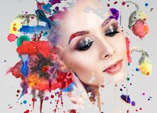 Portrait of young woman and colorful paint blots. Over gray background royalty free stock images