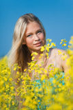 Portrait of a young woman in colza flowers Stock Photo