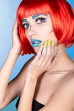 Female in red wig and in comic pop art make-up style on blue bac. Portrait of young woman in comic  pop art make-up style. Female in red wig on blue background Royalty Free Stock Photos