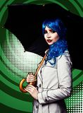 Portrait of young woman in comic pop art make-up style. Female with umbrella on green cartoon background stock images